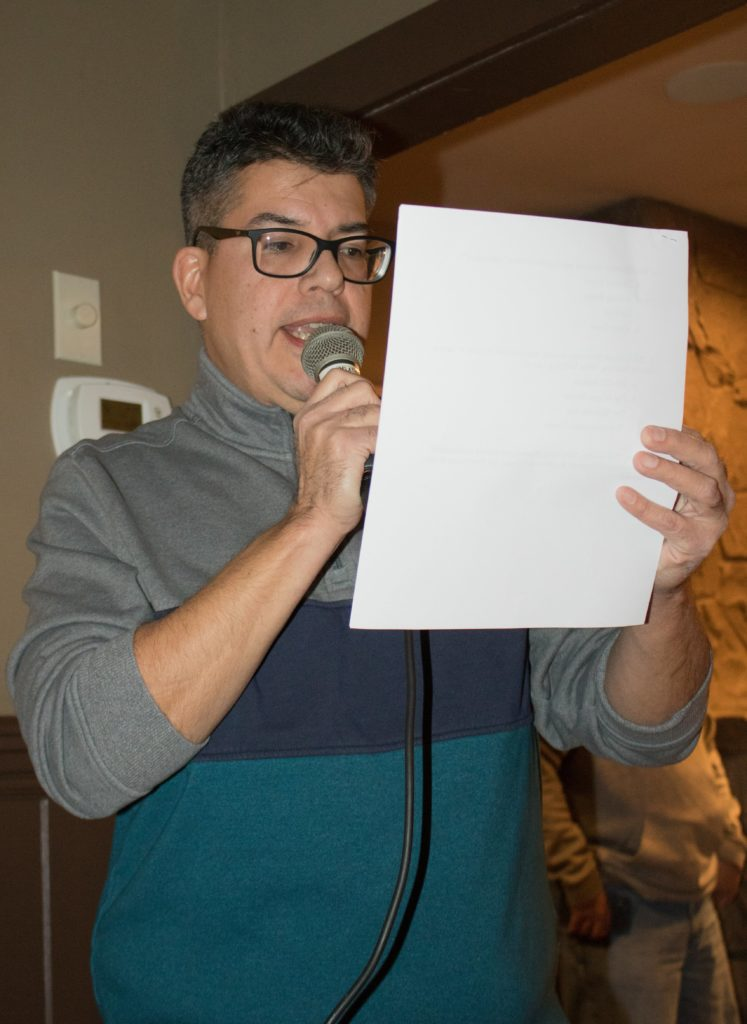 Man with a microphone reading from a sheet of paper