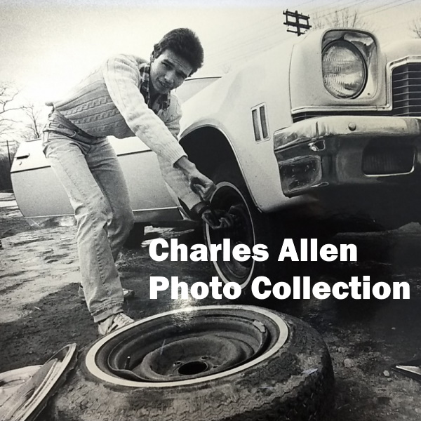 Charles Allen Photo Collection-White words over a photograph of a young man changing the tire on a white car, 1970s