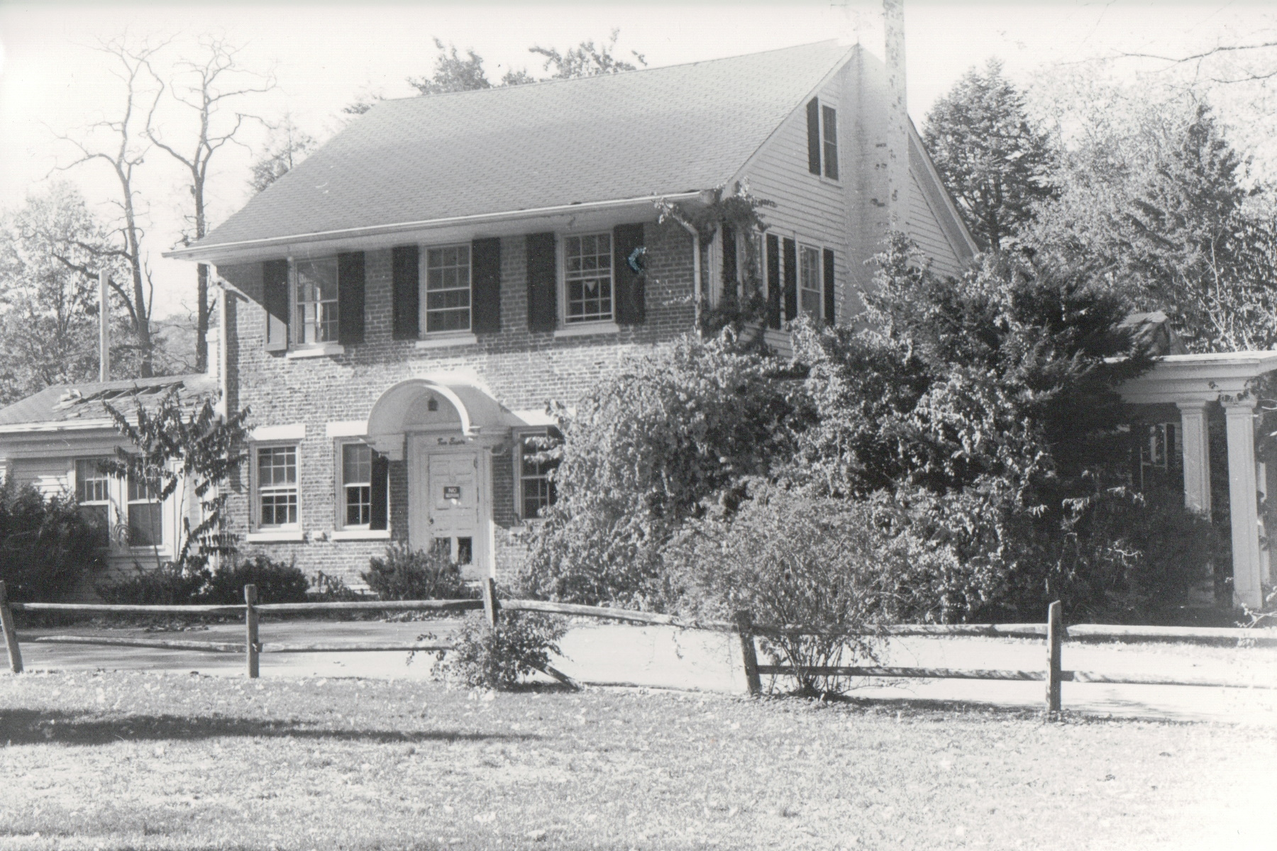 A black and white photograph of a colonial house from the street.