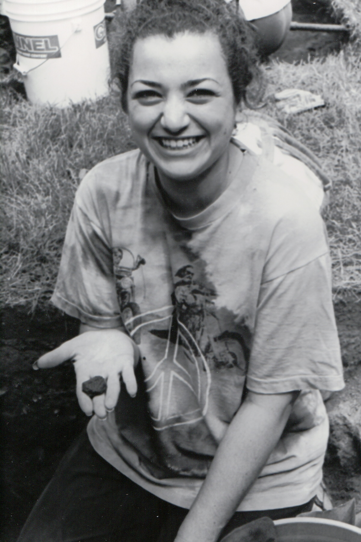 Black and white photo of a woman holding a pottery shard
