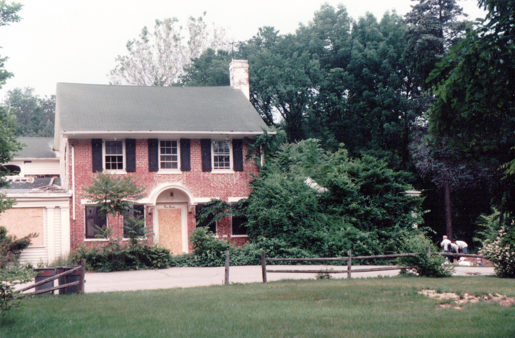 Color photograph of the Sheffield House with boarded up door and windows.