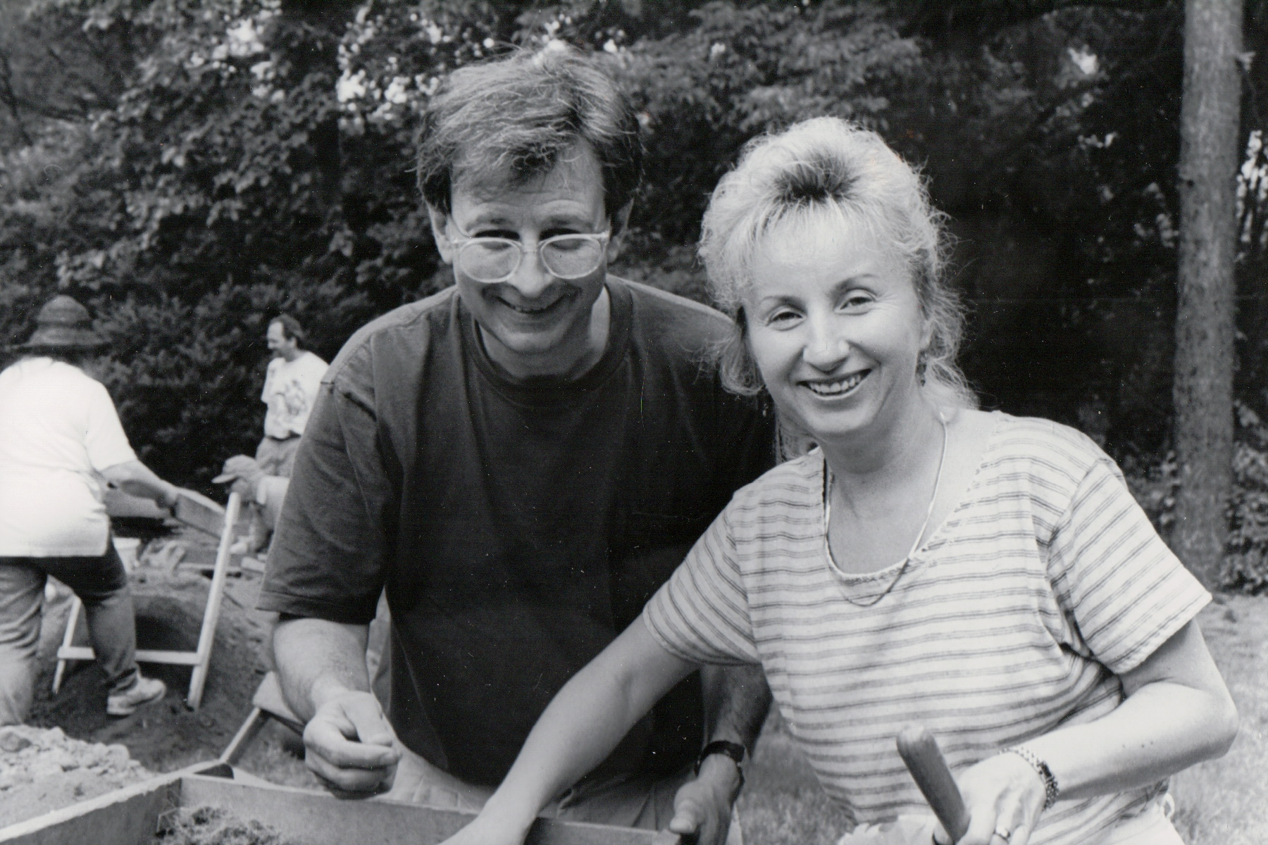 Black and white photo of a man and woman using a sifter at an archeological dig.