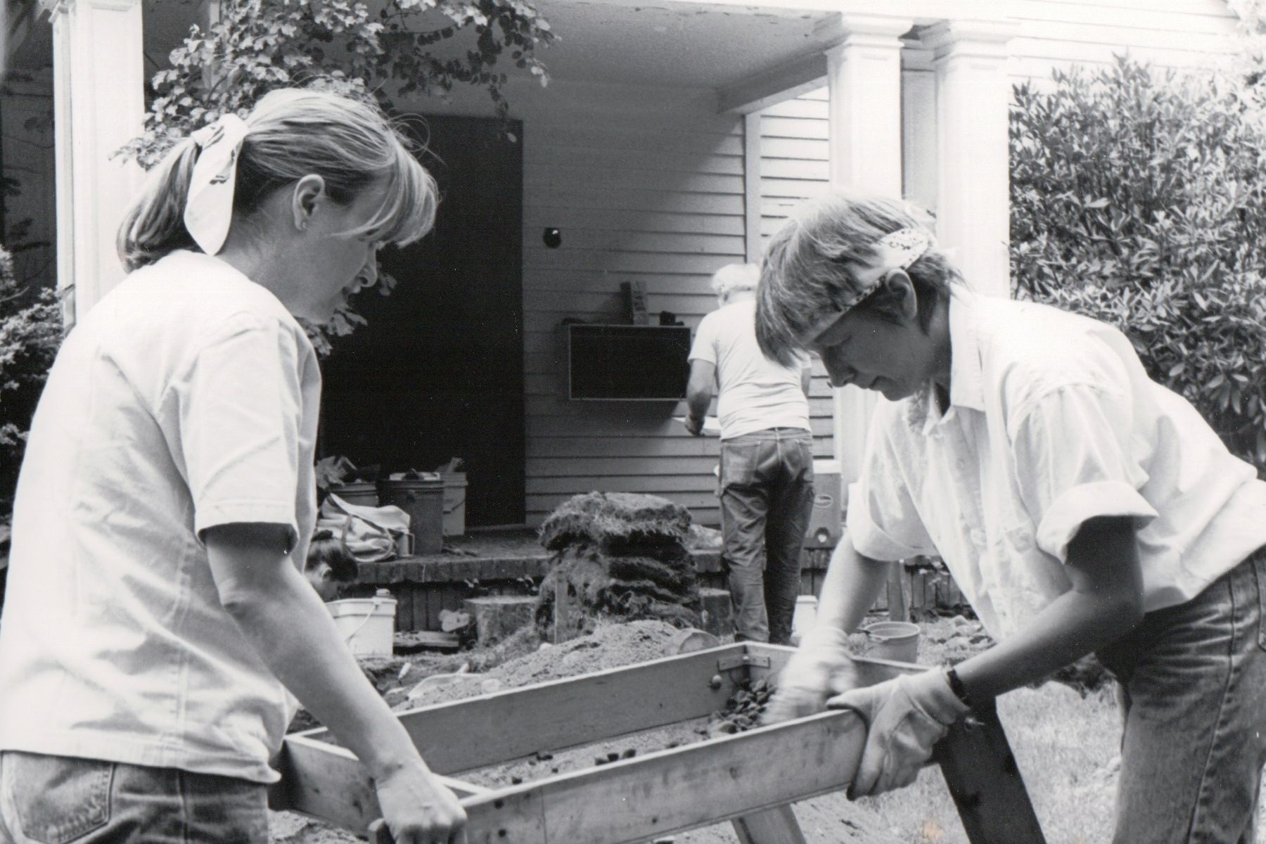 Black and white photo of two women sifting at an archeologial site