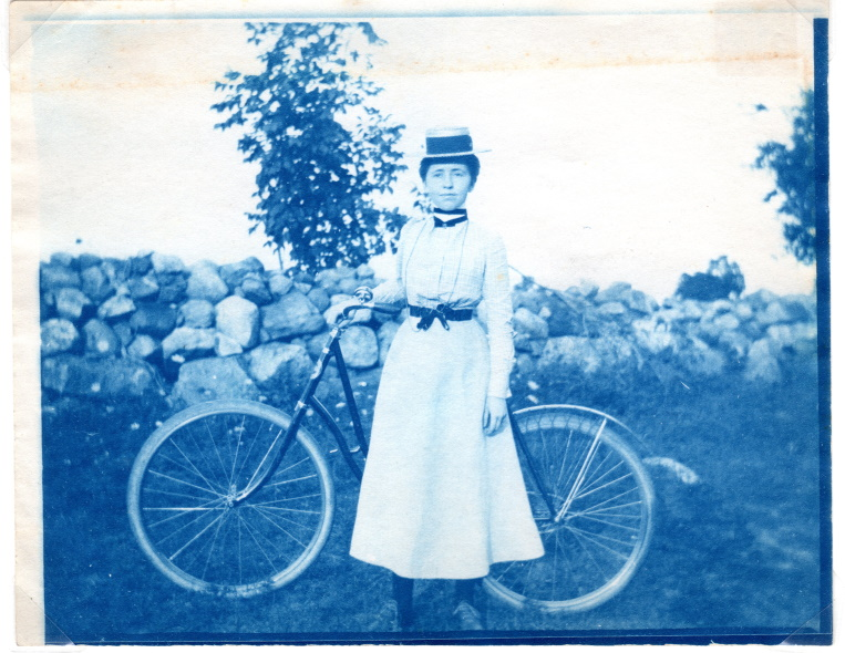 Blue tinted photograph of Annie Winter with her bicycle.